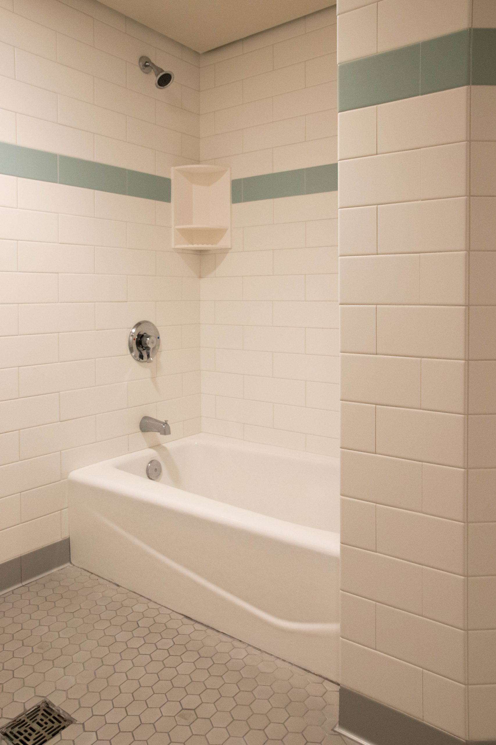 Community bathrooms of dorm hall: View of bathtub with soap shelf and temperature control