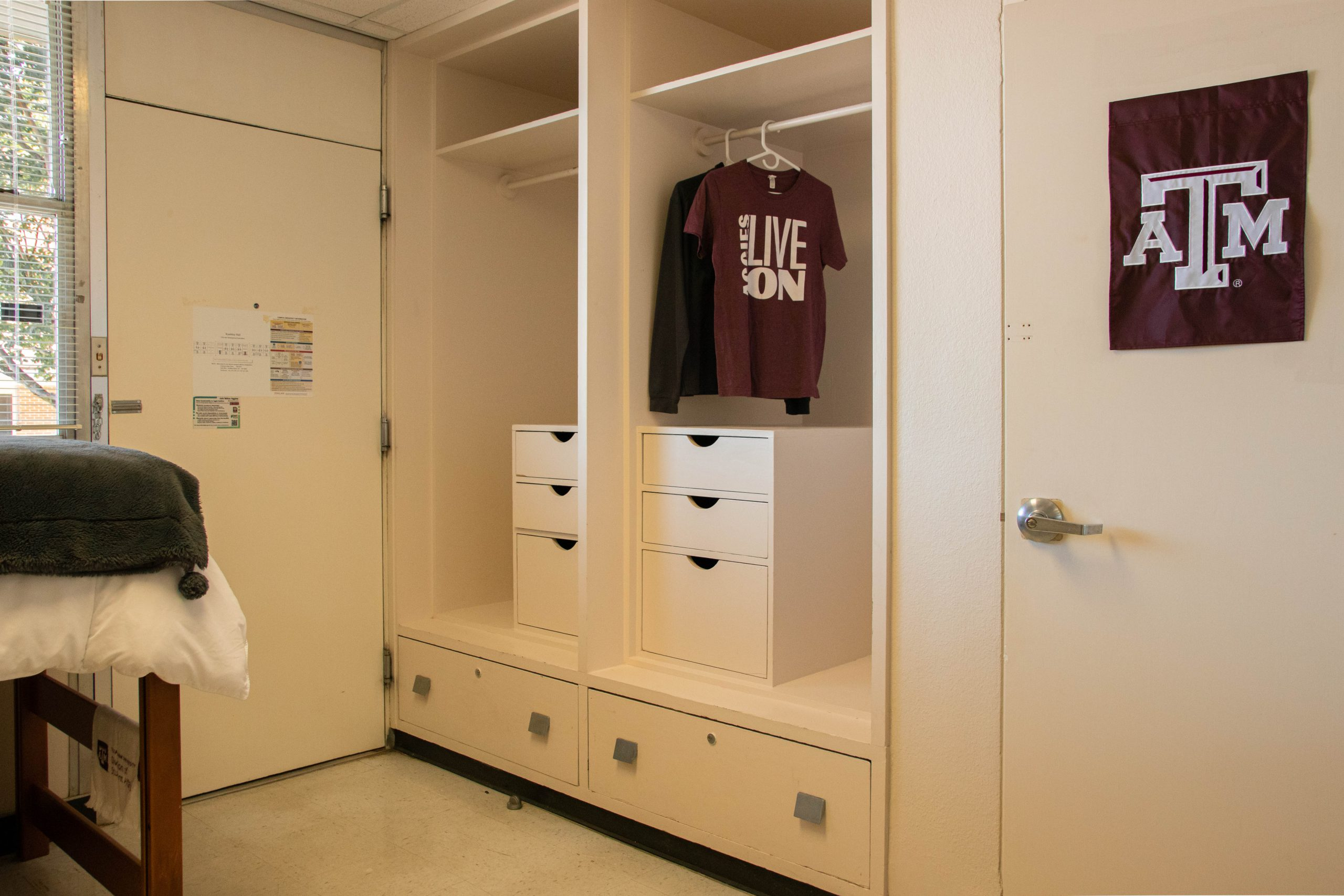 2 closet spaces that contains drawer and cabinet in each closet space, and view of entrance door