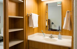 Interior of dorm hall: one sink that has a drawer and cabinet under it. One mirror, two towel holders, and one open-cabinet storage space