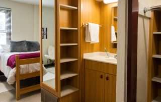 One twin-sized bed, one nightstand that has a drawer and cabinet. one sink that has a drawer and cabinet under it. One mirror, two towel holders, and one open-cabinet storage space