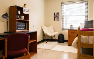 Interior of dorm room: one twin-size bed, one nightstand, one study desk and study chair, one open cabinet storage space